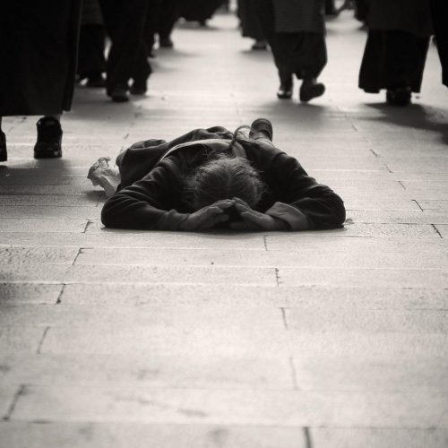 Discouragement: The Enemy's Greatest Attack- Monochromatic image of people walking around a man laying on the floor face down