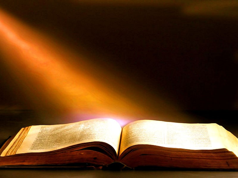 Follow God's Charge- An open bible with a ray of light shining on it