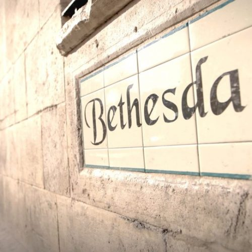 Step Out to Step In- Tiled sign that says Bethesda on stone wall