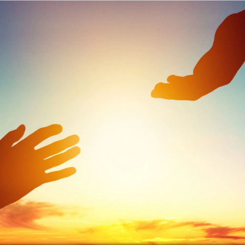 For Giving: Why We Should- Hand on left and hand on right reaching toward each other on a sunny day