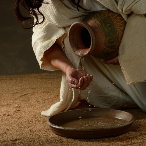 Things to Ponder- White clothed man crouched pouring water from a pottery jar onto his hand
