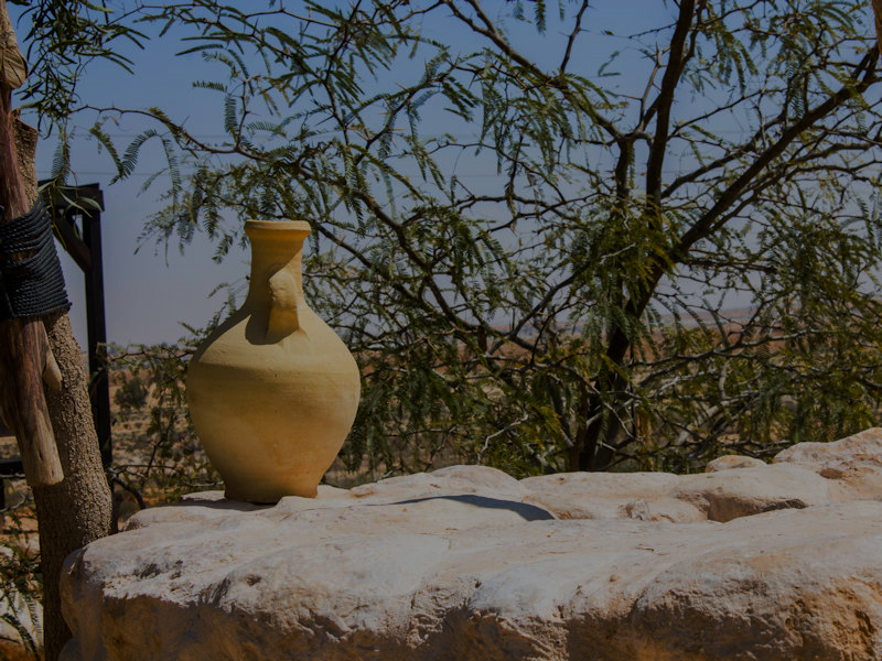 Living Water for the Soul- Ceramic water pot sitting on a well with tree in the background